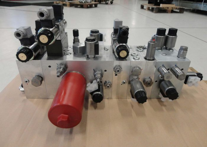 Manifold constructed out of several sections to drive the hydraulic system of a spreader